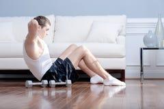 Homme faisant le Sit-ups dans la salle de séjour Image stock