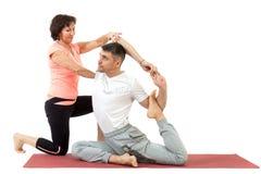 Homme faisant le yoga sous la direction d'un entraîneur photographie stock libre de droits