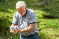 Homme faisant sa propre blanchisserie en nature Images libres de droits