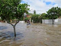 Homme faisant un cycle en bas de la rue inondée Image libre de droits