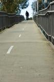 Homme faisant un cycle sur le passage supérieur de passerelle Images libres de droits