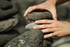 Homme faisant une tour avec des pierres Photographie stock libre de droits