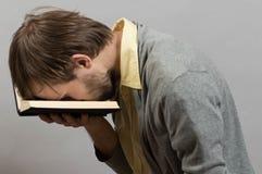 Homme fatigué d'un livre inintéressant Image libre de droits