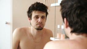 Homme fatigué qui s'est juste réveillé regardant sa réflexion dans le miroir et clignote clips vidéos