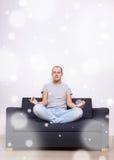 Homme fatigué s'asseyant sur le sofa dans la pose de yoga Image libre de droits