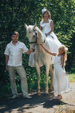Homme, femme habillée en tant que jeune mariée, fille et cheval blanc en parc Image stock