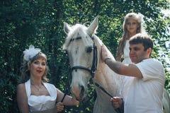 Homme, femme habillée en tant que jeune mariée, fille et cheval blanc en parc Image libre de droits