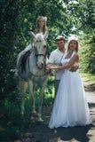 Homme, femme habillée en tant que jeune mariée, fille et cheval blanc en parc Photographie stock