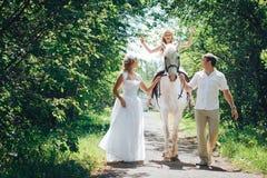 Homme, femme habillée en tant que jeune mariée, fille et cheval blanc en parc Photos libres de droits