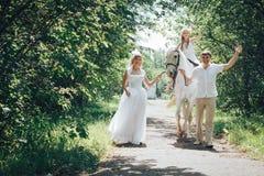 Homme, femme habillée en tant que jeune mariée, fille et cheval blanc en parc Photographie stock libre de droits