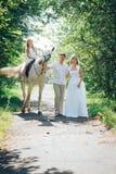 Homme, femme habillée en tant que jeune mariée, fille et cheval blanc en parc Photo stock