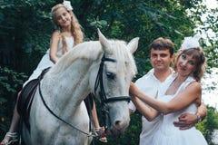 Homme, femme habillée en tant que jeune mariée, fille et cheval blanc en parc Photo libre de droits