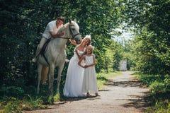 Homme, femme habillée en tant que jeune mariée, fille et cheval blanc en parc Images libres de droits