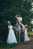 Homme, femme habillée en tant que jeune mariée, fille et cheval blanc en parc Photos stock