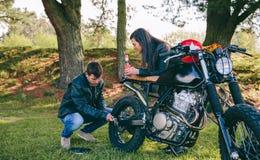 Homme fixant sa moto tandis que son amie le regarde images stock