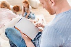 Homme focalisé à l'aide du comprimé numérique avec la famille tout près Image stock