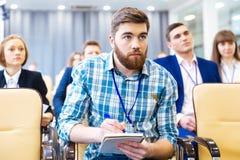 Homme focalisé écoutant et faisant des notes sur la présentation image stock