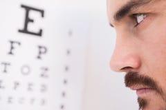 Homme focalisé sur des lettres d'essai d'oeil Images libres de droits