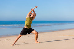 Homme folâtre faisant la gymnastique sur la plage images libres de droits
