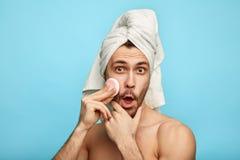 Homme fol avec plaisir tenant une protection de coton tout en s'inquiétant de sa peau image libre de droits