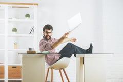 Homme fol cassant l'ordinateur portable Photos stock