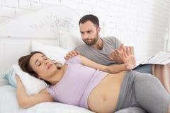 Homme fol réveillant la femme enceinte Images stock