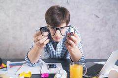 Homme fol regardant par des lunettes Photographie stock