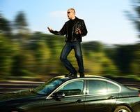 Homme fol se tenant sur la voiture mobile Photos libres de droits