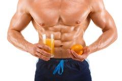 Homme formé et en bonne santé de corps jugeant un jus et une orange, abdominal formé, d'isolement sur le blanc Photo libre de droits