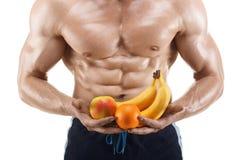Homme formé et en bonne santé de corps tenant des fruits frais, abdominal formé, d'isolement sur le fond blanc Image libre de droits