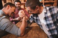 Homme fort bel ayant un match armwrestling Photographie stock libre de droits