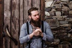 Homme fort brutal avec une barbe et tatouages sur ses mains habill?es dans les supports ?l?gants de v?tements sport sur le fond d image libre de droits
