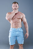 Homme fort brutal de bodybuilder posant dans le studio sur le backgroun gris Images libres de droits