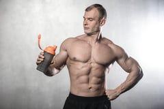 Homme fort brutal de bodybuilder posant dans le studio sur le backgroun gris Photo stock