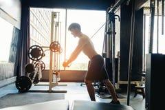 Homme fort de forme physique faisant l'exercice lourd sur la machine dans le gymnase Photo libre de droits