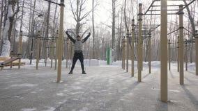 Homme fort faisant l'exercice accroupi avec l'extenseur de forme physique sur l'au sol de sports image libre de droits
