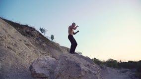 Homme fort pulsant sur la roche rugueuse et le combat gratuit s'exerçant 4K banque de vidéos