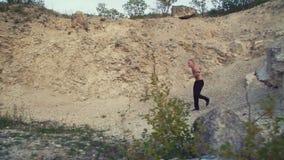 Homme fort pulsant sur la roche rugueuse 4K banque de vidéos