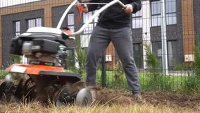 Homme fort travaillant avec le cultivateur d'essence sur labourer la cour de maison urbaine banque de vidéos