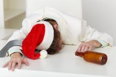 Homme fortement ivre dans le capuchon de Noël sur la table Image libre de droits