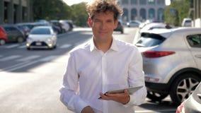 Homme frais d'affaires travaillant à la rue avec le comprimé au coucher du soleil dans le mouvement lent de ville banque de vidéos