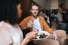 Homme frais s'asseyant dans le restaurant et parlant avec la fille Garçon s'asseyant au café avec le verre de l'eau à disposition Photo libre de droits
