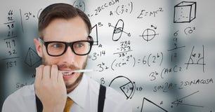Homme frustrant d'affaires avec le stylo dans la bouche contre les graphiques gris troubles de bureau et de maths photo stock