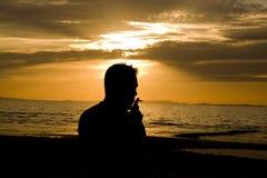 Homme fumant par la plage Photographie stock libre de droits