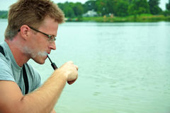 Homme fumant une pipe Photographie stock libre de droits