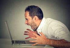 Homme furieux fâché d'affaires criant à l'ordinateur images stock