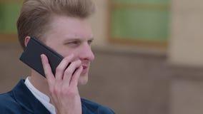 Homme futé de téléphone invitant le téléphone portable la nuit dans la ville Jeune homme beau d'affaires parlant sur le sourire d banque de vidéos