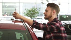 Homme gai à l'aide du téléphone intelligent montrant des clés de voiture à l'appareil-photo posant au concessionnaire banque de vidéos