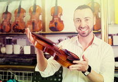 Homme gai achetant les violons traditionnels Images stock
