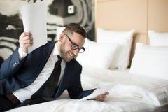 Homme gai avec des papiers sur le lit images stock